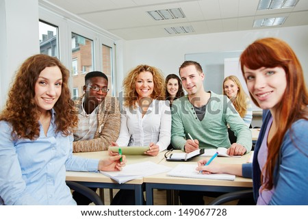 Many smiling students in university class working as a team - stock photo