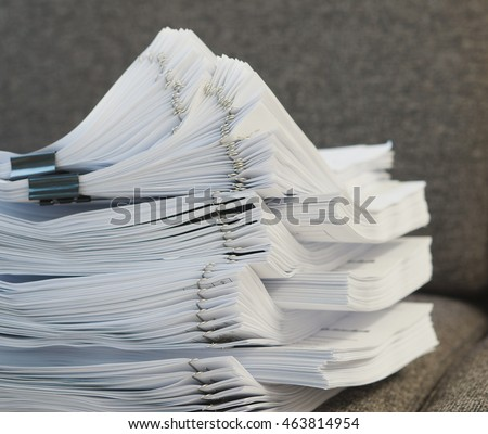 Many stack of document was put  on sofa at office.