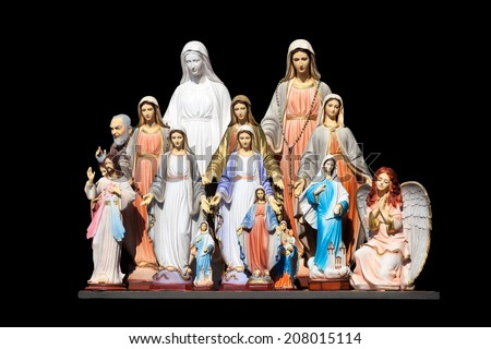 Many statues of the Virgin Mary on a black background. - stock photo