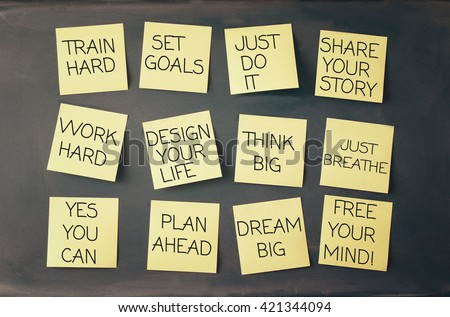 many sticky notes attached to blackboards with handwriting text - stock photo