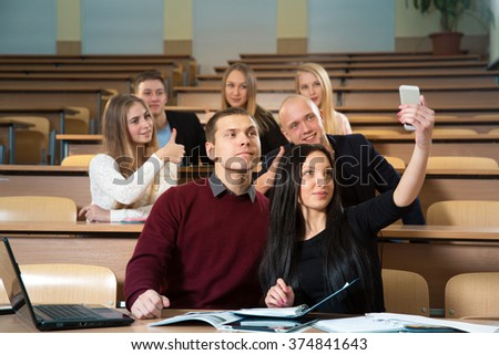 Many students in university classroom on seminar take a selfie on phone camera