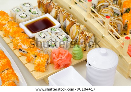 many sushi rolls served with wasabi, ginger and soy sauce - stock photo