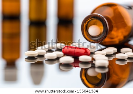 many tablets with a glasbegh���¤ter. symbolic photo for addiction and costs in medicine and medicines. - stock photo