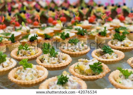 many tartlets with meat salad under mayonnaise and parsley on buffet table, shallow DOF - stock photo
