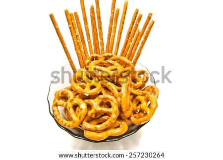 many tasty salted pretzels and breadsticks on white - stock photo