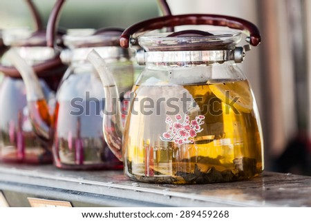 Many teapots with different colors fruit tastes of tea. - stock photo