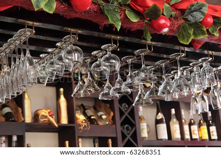 Many the turned glasses hang in a bar