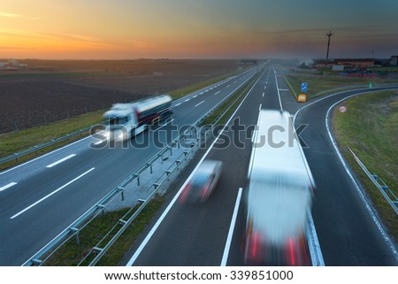 Many trucks driving in motion blur on the freeway at beautiful sunset. Rush hour on the highway near Belgrade - Serbia. - stock photo