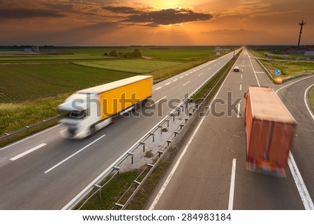 Many trucks driving in motion blur on the freeway towards the setting sun. Rush hour on the motorway near Belgrade - Serbia. - stock photo