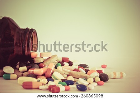 Many type of drugs pills capsules and medicine poring from the bottle with white isolation background in vintage retro color. Medical manufacturing industry concept. - stock photo