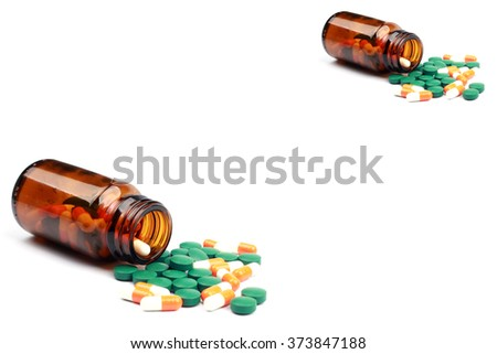 Many type of drugs pills capsules and medicine poring from the bottle with white isolation background. Medical manufacturing industry concept.