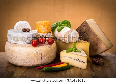 many types of french cheeses with basil, tomatoes and peppers