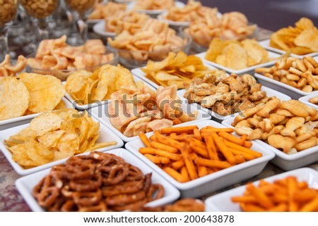 Many types of savoury snack in white dishes - stock photo