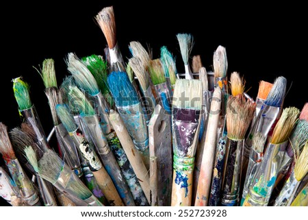 many used brushes for painting and black background