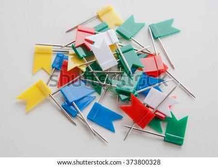 Many varicolored plastic push pins looks like small flags - stock photo
