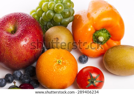 Many Variety fresh fruit(colorful sweet pepper, pimenta, bell pepper, pimento, blueberry, green grape, red cherry, gold kiwi, red apple, green lime, Grapefruit, tomato) isolated white at the studio. - stock photo