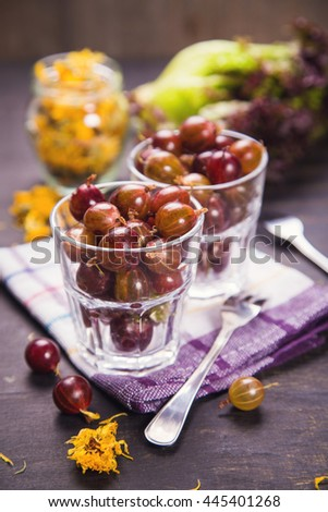 many wet raw ripe gooseberry in glass with dry calendula - stock photo