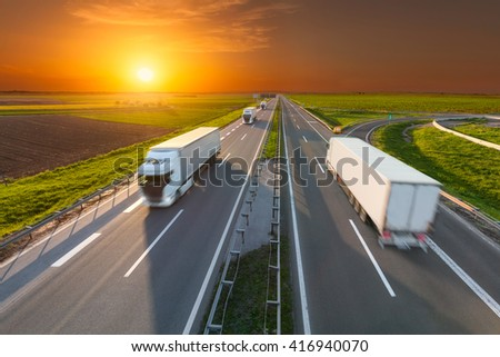 Many white trucks driving towards the sun. Fast blurred motion drive on the freeway at beautiful sunset. Freight scene on the motorway near Belgrade, Serbia. - stock photo