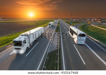 Many white trucks in line and fast travel bus driving towards the sun. Speed blurred motion drive on the freeway at beautiful sunset. Transport travel scene on the motorway near Belgrade, Serbia. - stock photo