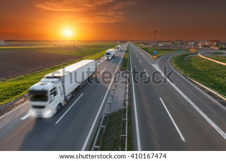Many white trucks in line driving towards the sun. Fast blurred motion drive on the freeway at beautiful sunset. Freight scene on the motorway near Belgrade, Serbia. - stock photo