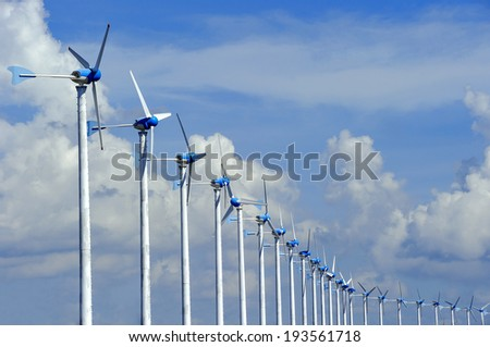 Many wind turbines produce electricity on blue sky. - stock photo