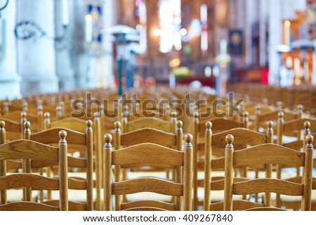 Many wooden chairs in a church - stock photo