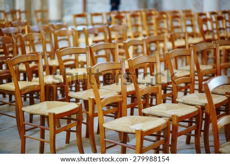 Many wooden chairs in a French church - stock photo
