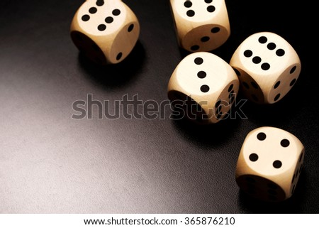 Many wooden dices on a black background. - stock photo
