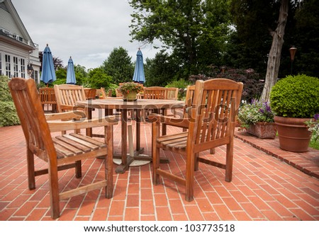 Many wooden teak tables and chairs on brick patio in cafe or restaurant