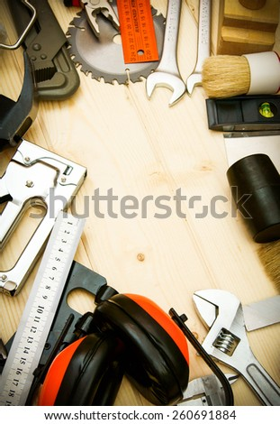 Many working tool. The different working tools (plane, saw, mallet, stapler and others) on a wooden background. - stock photo