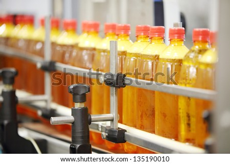 Many yellow plastic bottles with fresh beer go on conveyor at large brewery. - stock photo