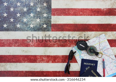 Map, compass, passports and sunglasses on vintage American flag canvas background - stock photo