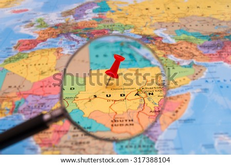 Map of Sudan with magnifying glass and red pin - stock photo
