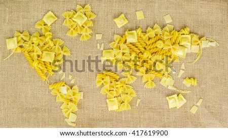 map of the world made of raw pasta on brown fabric background with texture - stock photo