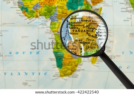 Map of United Republic of Tanzania through magnigying glass - stock photo