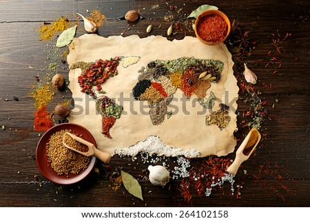 Map of world made from different kinds of spices on wooden background - stock photo