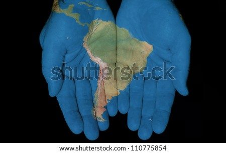 Map painted on hands showing concept of having South America in our hands - stock photo
