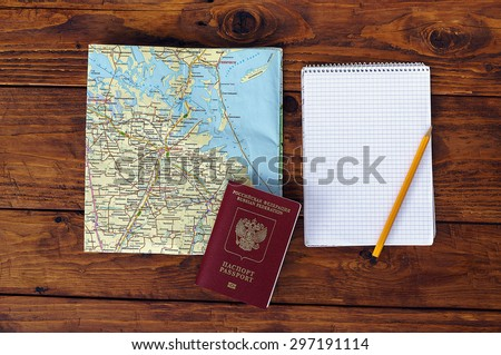 map, passport, notebook and cup of coffee on wooden table - stock photo