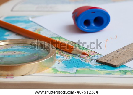 Map, pencil and magnifying glass - stock photo