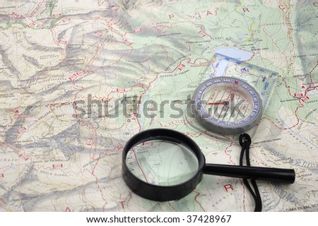 Map with compass and magnifying glass. On the map are mountains, a valley and a lake.