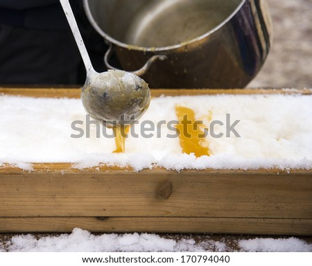 Maple syrup being ladled onto snow as a winter treat - stock photo