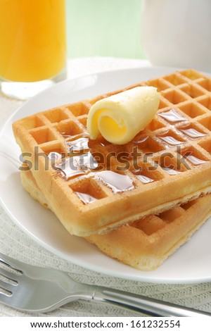 Maple syrup on a stack of waffles - stock photo