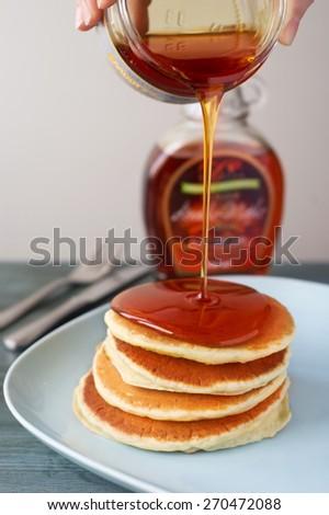 Maple syrup pouring onto pancakes.  - stock photo