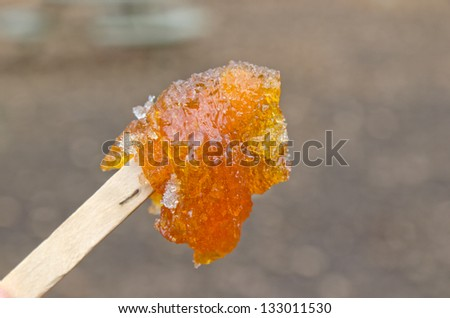 Maple taffy on a stick during sugar shack period - stock photo
