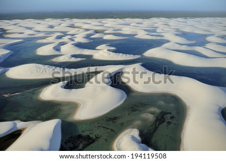 Maranhao state, Brazil - August. 21. 2010 : Aerial view of Lencois Maranhenses National Park, Brazil, low, flat, flooded land, overlaid with large, discrete sand dunes with blue and green lagoons - stock photo