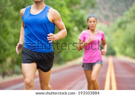 Marathon active running fitness athlete couple training on road. Multiracial female blurred in background - fit healthy male runner in front. Lifestyle in nature. - stock photo