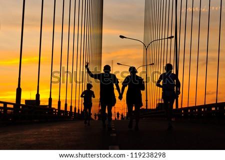 Marathon runner running on bridge in the morning - stock photo