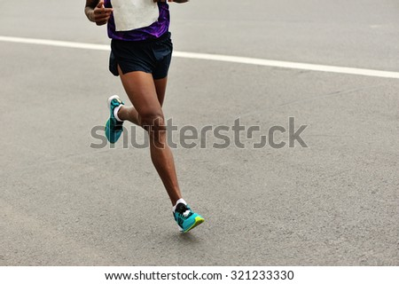 Marathon runner running on city road - stock photo