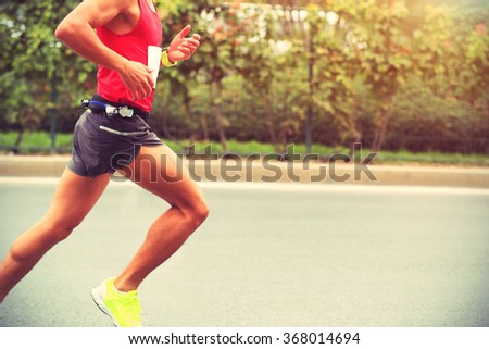 Marathon runner running on city road - stock photo