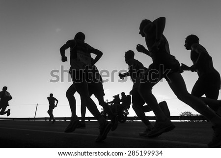 Marathon Runners Black White Durban - South Africa - 31 May - 2015. Comrades Marathon runners on the road action closeup dawn silhouettes . - stock photo